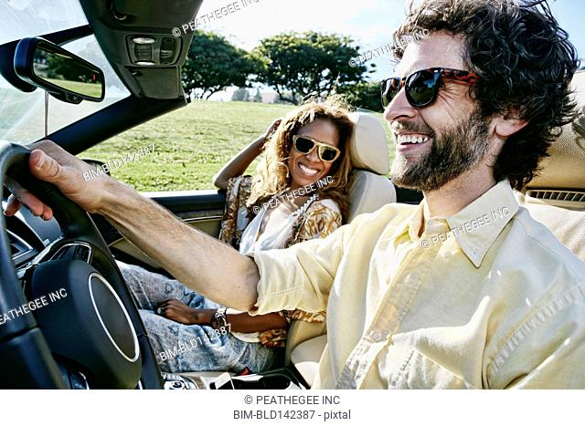 Couple driving together in convertible