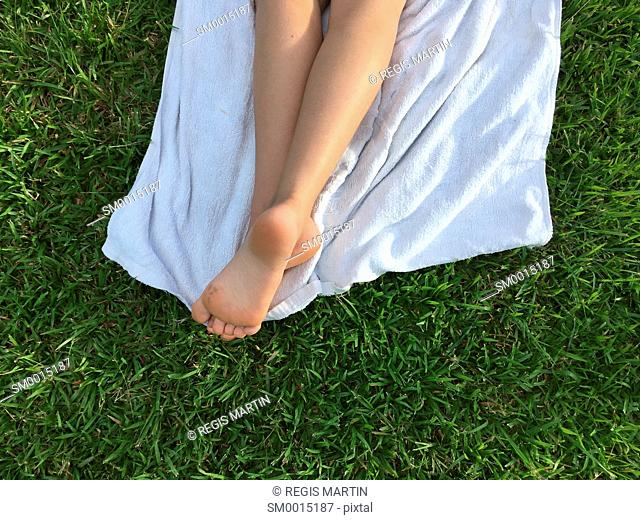 legs of a young girl resting on a white towel on the grass