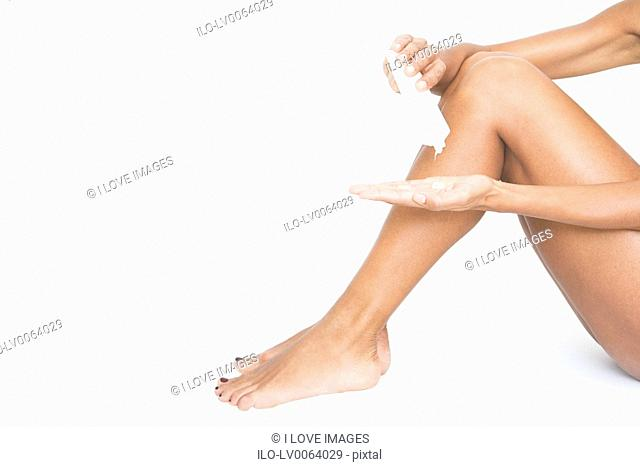 A woman applying moisturiser to her legs