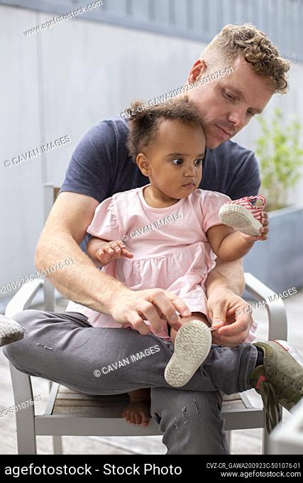 A dad helping his young daughter put her shoes on
