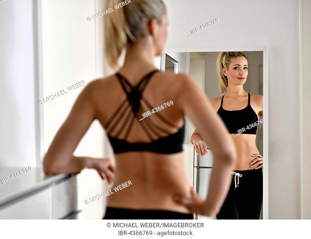 Young woman with sports bra and sweatpants looks at herself in the mirror