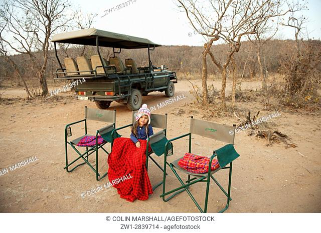 Young girl (model released) sitting in chair in the bush with game drive vehicle in background, Ant's Hill Reserve, near Vaalwater, Limpopo province