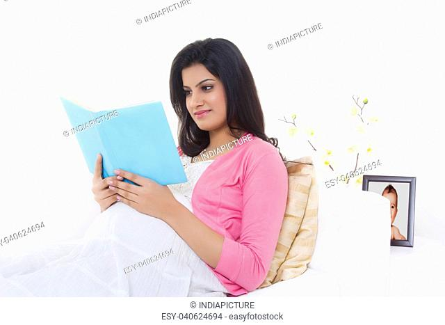 Pregnant woman reading a book on a couch