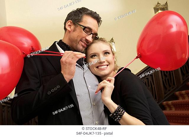 Amorous couple with balloons on a stairway