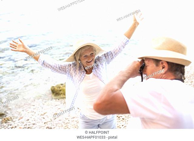 Senior man taking picture of his happy wife on the beach