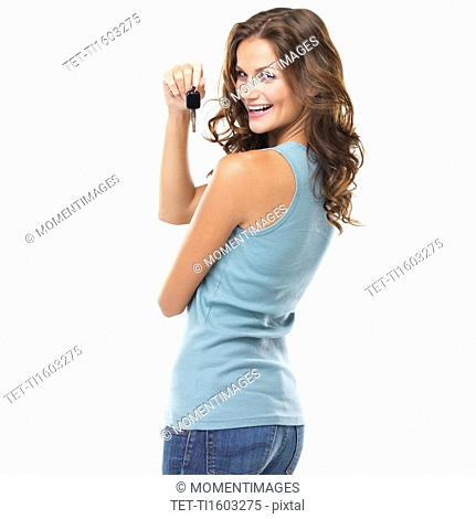 Studio portrait of beautiful woman turning around and holding car keys