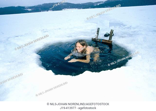 Hole in the ice, having a cold bath after the sauna. Jämtland, Sweden