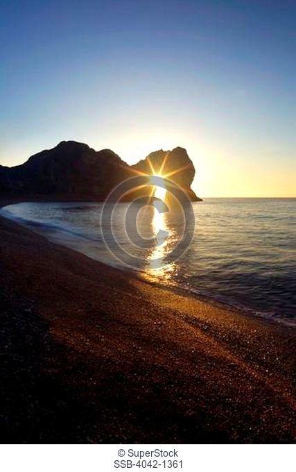 England, Dorset, Portland Bill, Sun shining through Pulpit Rock