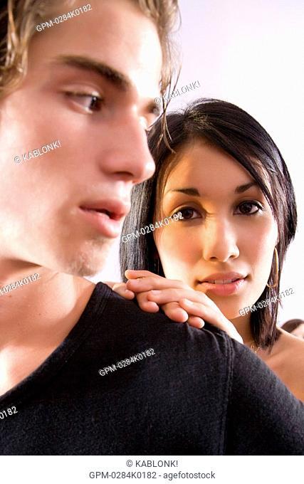 Close-up of serious young man glancing back at young woman