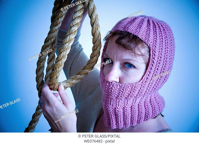 Young woman, wearing a knitted hood and holding a thick rope, posing