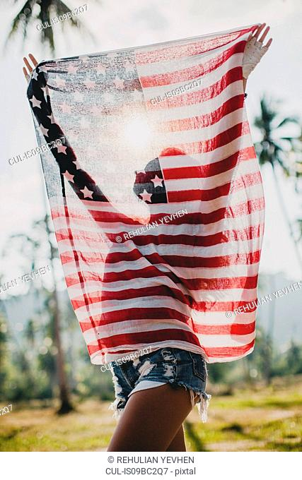 Young woman holding up American flag, Krabi, Thailand