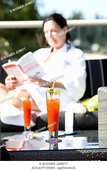 A mature woman relaxes at the outdoor patio with a cocktail while visiting the Kingfisher Resort and spa. Courtenay, Vancouver Island, British Columbia, Canada