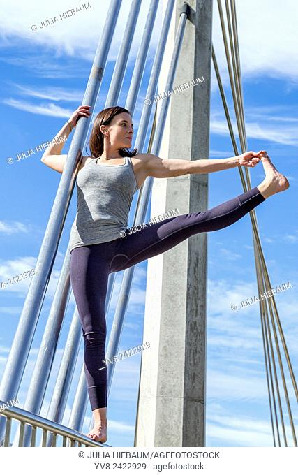 Extended hand to toe yoga pose performed on a bridge, San Diego, California