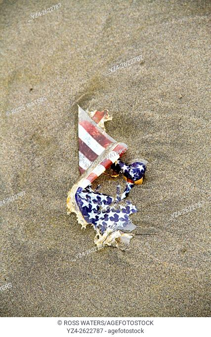A damaged American flag on the beach