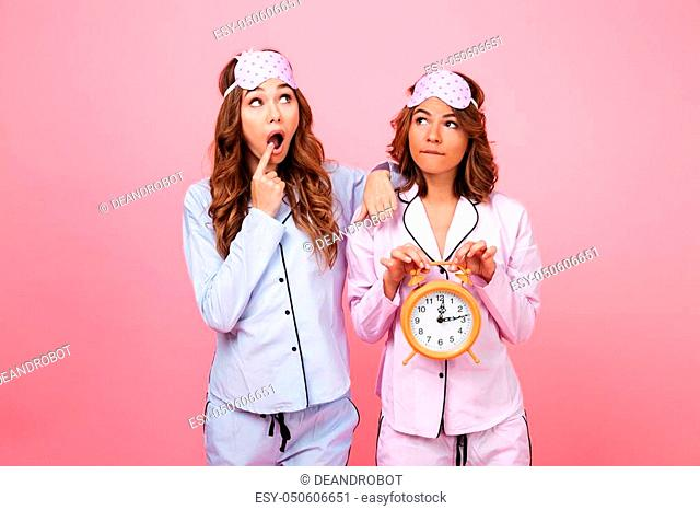 Image of two shocked friends women in pajamas isolated over pink background holding alarm clock. Looking aside