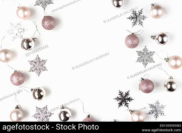 White and silver Christmas ornaments and gift on white background top view. Christmas and Holidays greeting card, frame, banner. New Year. Noel