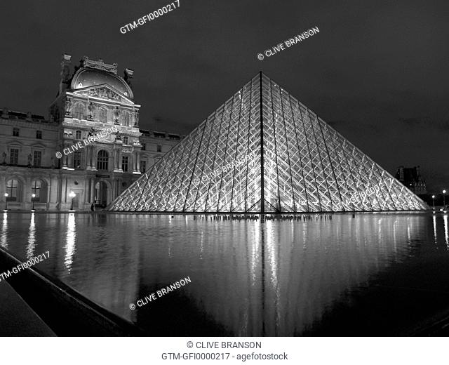 View of the glass triangular dome of the Louvre in Paris France reflected into water at night