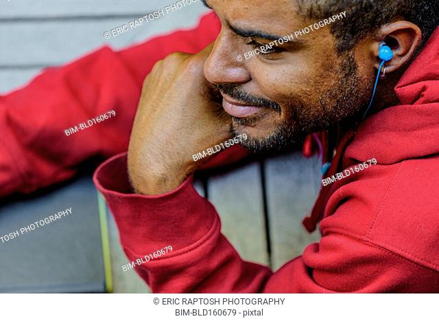 Close up of mixed race man listening to earbud