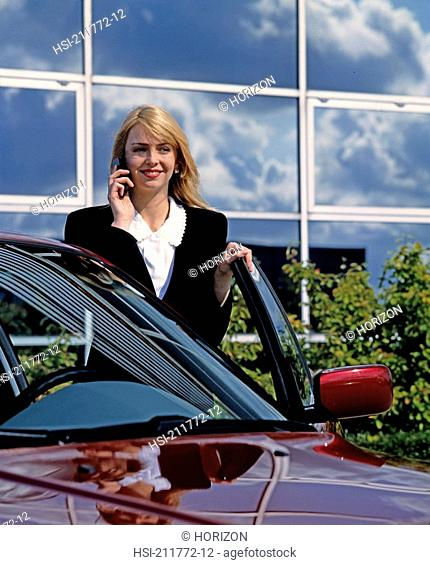 Businesswoman talking over cell phone standing with car in United Kingdom, Europe