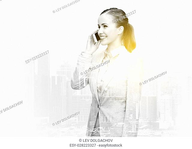 business, technology and people concept - young smiling businesswoman calling on smartphone over city buildings and double exposure effect