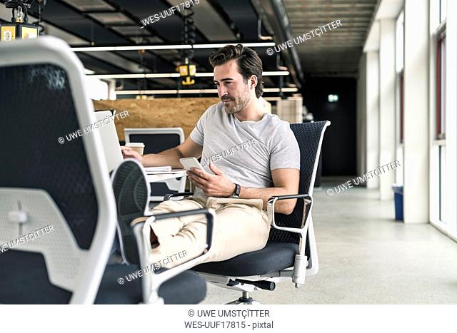 Young businessman working relaxed in modern office, using smartphone and laptop