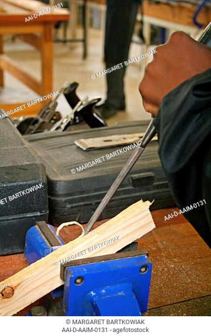 School boy chiselling with hammer in woodwork classroom, St Mark's School, Mbabane, Hhohho, Kingdom of Swaziland