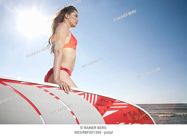 Germany, St Peter-Ording, young woman with stand up paddling surfboard at beach