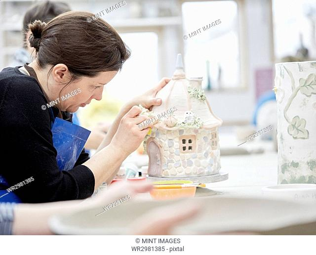 A woman working on a decorated pottery cottage with a sponge, decorating or finishing a piece