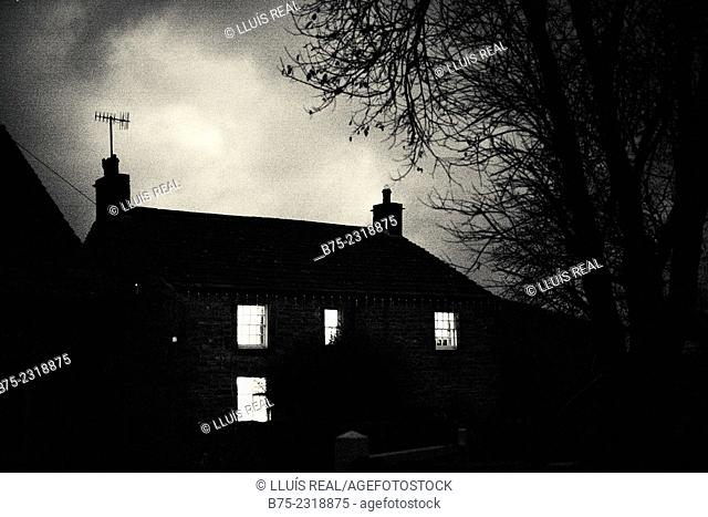 Black and white silhouette of a house with a tree at the sunset with the light on in the windows, Buckden, Skipton, Yorkshire Dales, England, UK