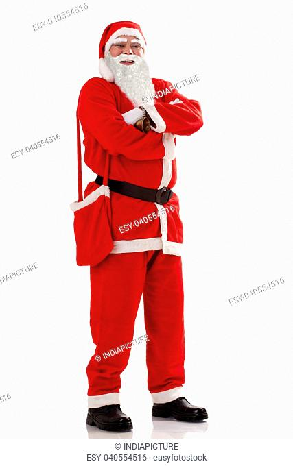 Full length portrait of smiling Santa Claus with arms folded standing over white background