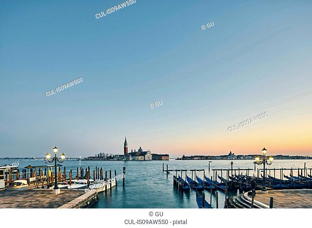 Distant view of rows of moored gondolas on waterfront at dusk, Venice, Italy