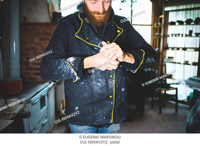 Bearded mid adult man squeezing clay in hands, looking down