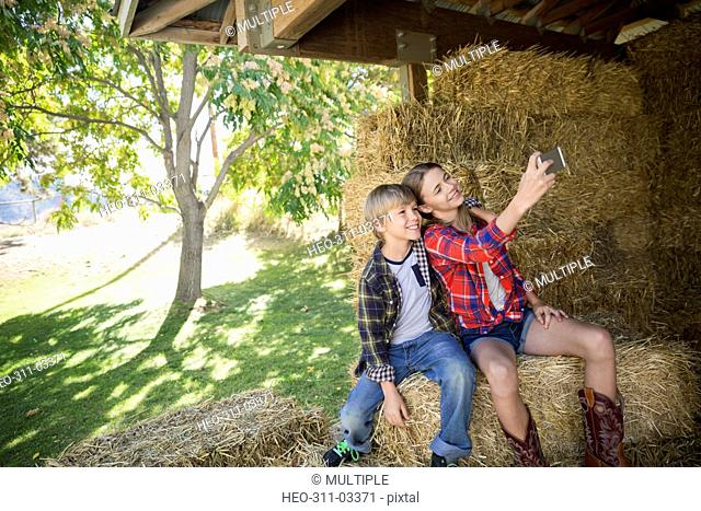 Brother and sister with camera phone taking selfie on hay bale in barn