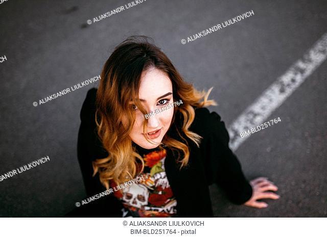 Caucasian woman sitting on street
