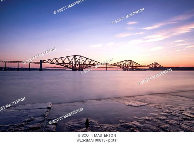 UK, Scotland, Fife, Edinburgh, Firth of Forth estuary, Forth Bridge, Forth Road Bridge and Queensferry Crossing in the background at sunset