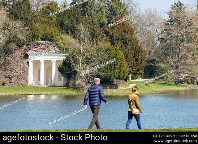 05 April 2020, Saxony-Anhalt, Wörlitz: Visitors walk along Lake Wörlitz in the Wörlitz Park, the World Heritage Garden Kingdom of Dessau-Wörlitz
