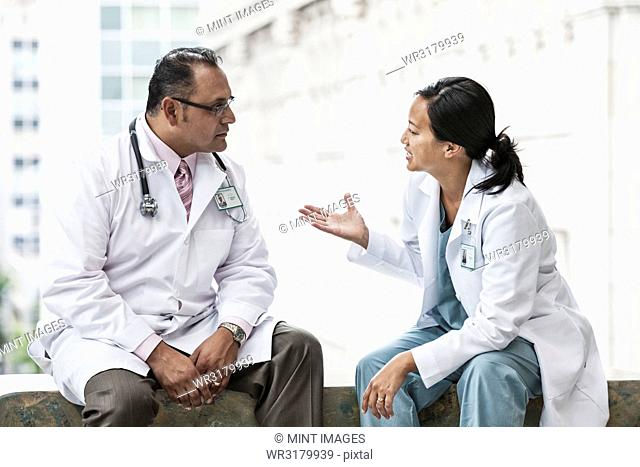 Hispanic man and Asian woman doctors conferring over a case in a hospital