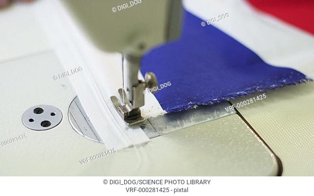Close up footage of a person using a sewing machine on fabric