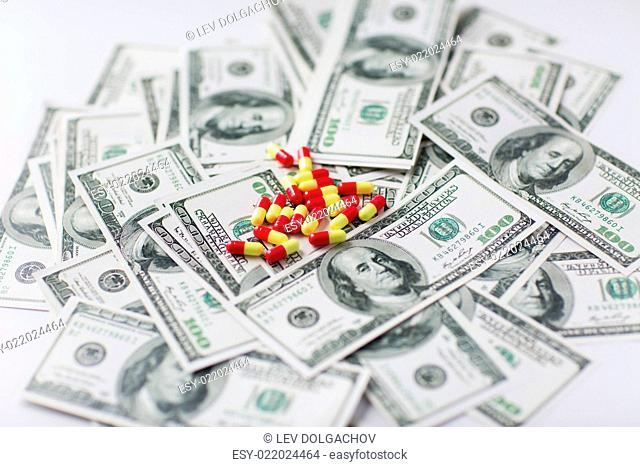 medicine, finance, health care and drug trafficking - medical pills or drugs and dollar cash money on table