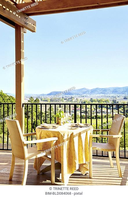 Private dining table and chairs on a restaurant deck overlooking wine country at a luxury resort in Napa Valley, California