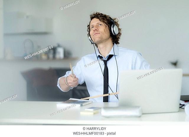 Businessman wearing headphones and drumming on his desk