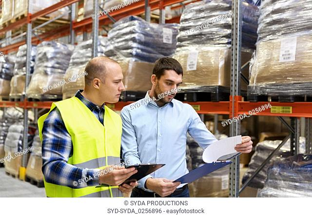worker and businessman with clipboard at warehouse