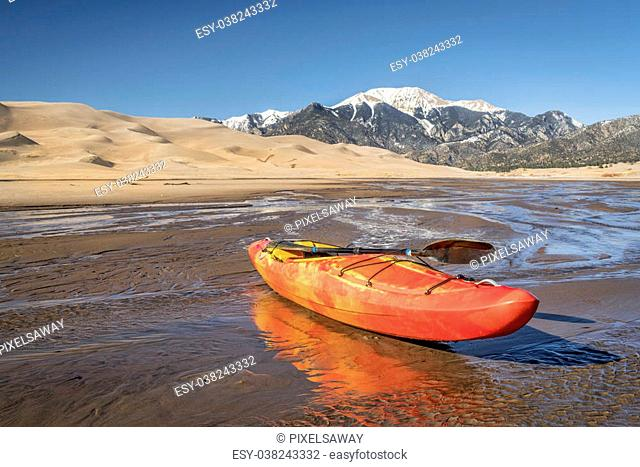 whitewater kayak in shallow waters of Medano Creek with Great Sand Dunes and Sangre de Cristo Mountains in background