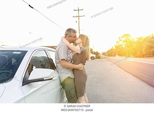 Couple on a road trip taking a break kissing each other