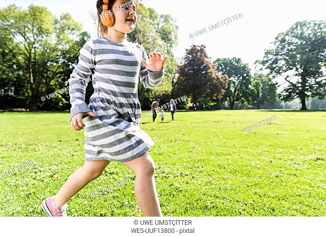 Girl with family in background wearing headphones in a park