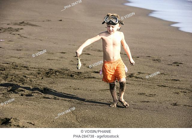 Boy holding a fish on a beach in Guatemala