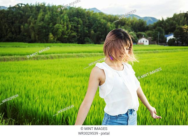 A young woman in a white shirt and jeans with hands outstretched, standing in open space by rice paddy fields