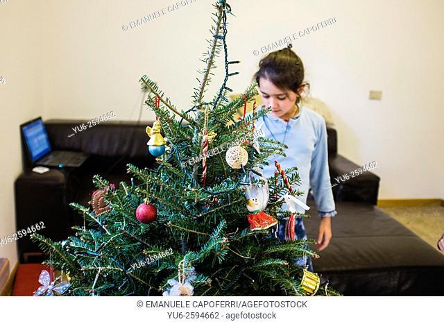 Girl preparing the Christmas tree at home