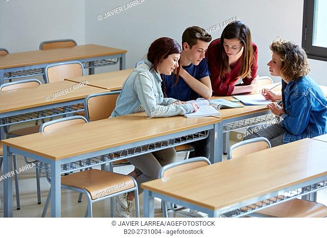 Students studying at desk in classroom