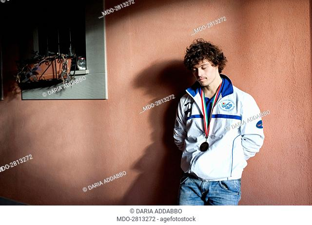 The captain of the paralympic swimming Italian team suffering from Down syndrome Marco Marzocchi posing for a photocall resting against an outer wall at home
